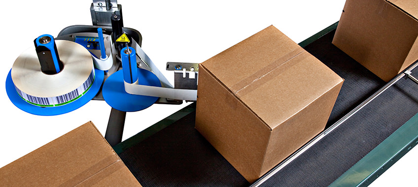 Label applicator sticks labels onto boxes passing on conveyor belt