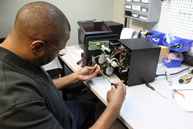 man working on a standalone labeling printer